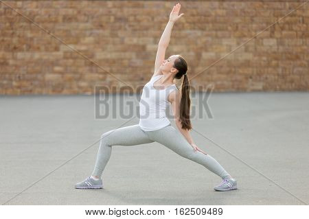 Sporty beautiful young woman practicing yoga, standing in Reverse Warrior exercise, Viparita Virabhadrasana pose, working out, wearing sportswear, outdoor full length, brick wall background