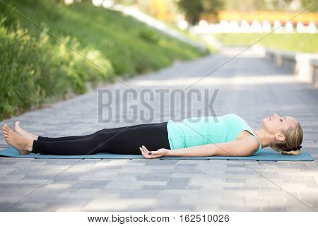 Sporty attractive young woman practicing yoga, lying in Dead Body exercise, Savasana, Corpse pose, working out, wearing sportswear, outdoor full length, street background, summer light, pavement