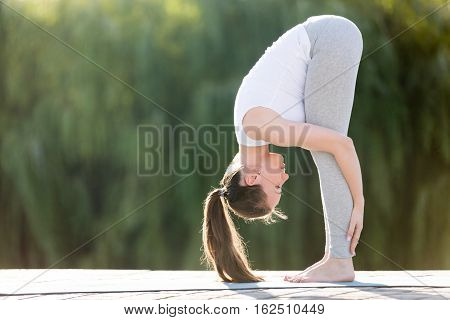 Sporty smiling attractive young woman practicing yoga, doing standing forward bend, head to knees exercise, uttanasana pose, working out, wearing sportswear, outdoor full length, street background