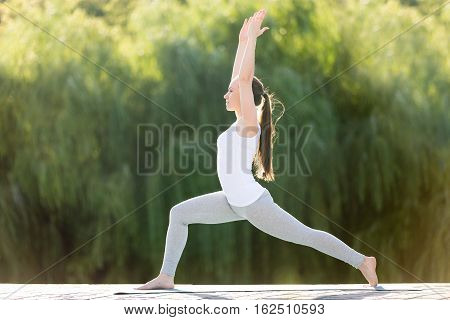 Sporty attractive young woman practicing yoga, standing in Warrior one exercise, Virabhadrasana 1 pose, working out, wearing sportswear, outdoor full length, street background