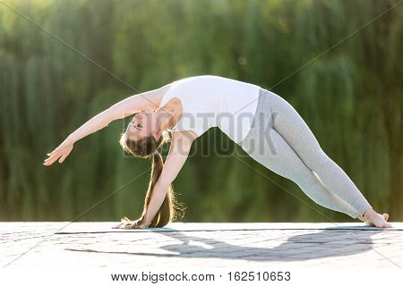 Sporty beautiful young woman practicing yoga, standing in Bending Side Plank exercise, vasistasana pose, working out, wearing sportswear, outdoor full length, summer park background