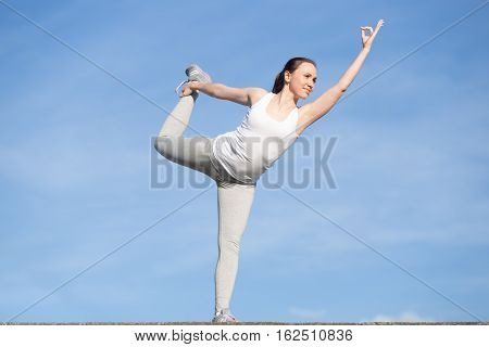 Sporty young woman practicing yoga, standing in Lord of the Dance exercise, Natarajasana pose, working out, wearing sportswear, outdoor, clear blue sky background