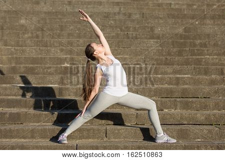 Sporty attractive young woman practicing yoga, standing in Reverse Warrior exercise, Viparita Virabhadrasana pose, working out, wearing sportswear, outdoor, stone stair background with a shadow