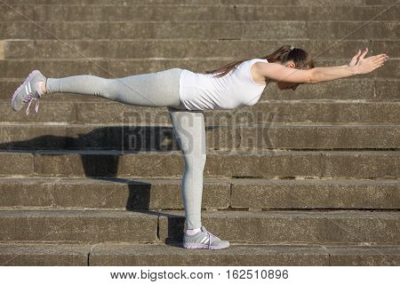 Sporty attractive young woman practicing yoga, standing in Warrior Three exercise, Virabhadrasana 3 pose, working out, wearing sportswear, outdoor, stone stair background with a shadow