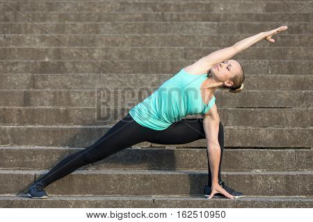Sporty attractive young woman practicing yoga, standing in Extended Side Angle exercise, Utthita parsvakonasana pose, working out, wearing sportswear, outdoor, urban stone stair background