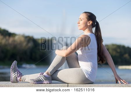 Sporty smiling attractive young woman practicing yoga, sitting in Half lord of the fishes exercise, Ardha Matsyendrasana pose, working out, outdoor full length, fountain explosion background, profile