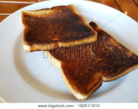 Burnt toast bread on white dish on wooden table background