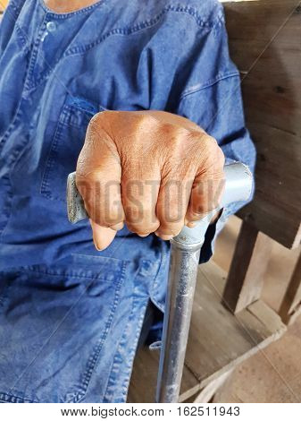 closeup hand of an old asian male with Thai traditional blue shirt holding a walking stick or a cane
