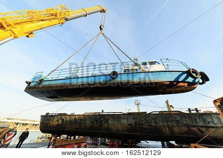 MOSCOW, RUSSIA - NOVEMBER 11, 2016: State Unitary Enterprise Mosvodostok performs recovery vessels on coastal winter parking. The ship suspended from a chain slings.
