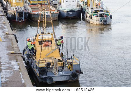 MOSCOW, RUSSIA - NOVEMBER 11, 2016: State Unitary Enterprise Mosvodostok performs recovery vessels on coastal winter parking. Several workers slingers hooked to the vehicle chain slings.