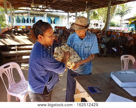 CHIANG RAI THAILAND - DECEMBER 19 : Unidentified asian officer giving old people suffering from leprosy clothing on December 19 2016 in Chiang rai Thailand.