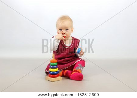 A shot of an adorable baby girl playing with wooden toys.