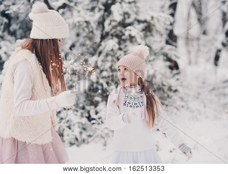 Two child girls having fun in snow outdoors. Playing with sparklers. Wearing knitted winter clothes. Togetherness. Christmas celebration.