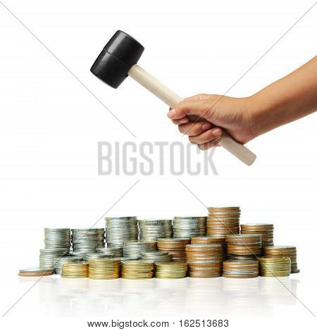 Hand holding a rubber hammer with coins stack, Concept of budget cuts, savings, recession.