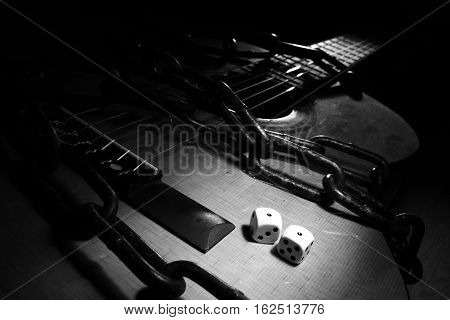 A black and white photo with film noir vibes of a pair of `snake eyes` watching you on a chained acoustic guitar.