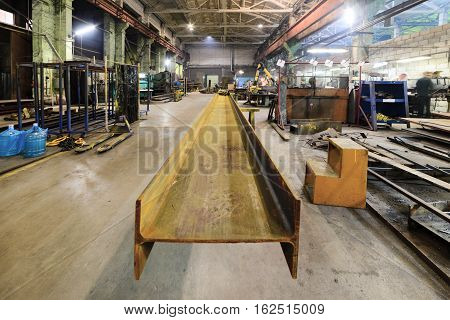 Rusty steel I-beams. Plot welding machine factory.