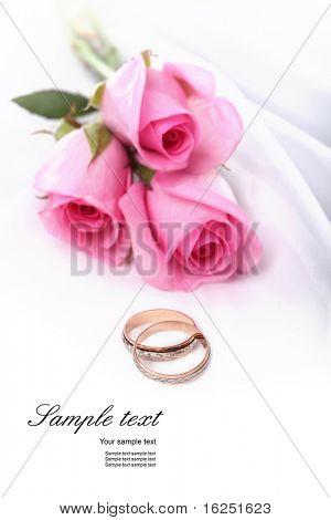 anéis de casamento e rosas rosa