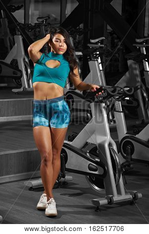 Young slim latina woman  in gym bike cycling background