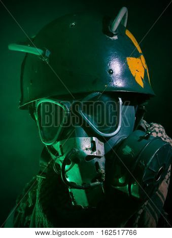 A portrait of a guy with gasmask and helmet, surrounded by green fog/smoke. Strong dystopia/post apocalyptic vibe.