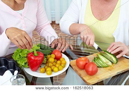 Mature women cutting vegetables for vegetarian salad