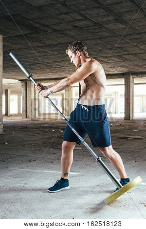 Front view of man with naked torso training with crossbar in hands outdoor.