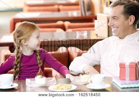 Little girl and her father dining at cafe at Father s Day