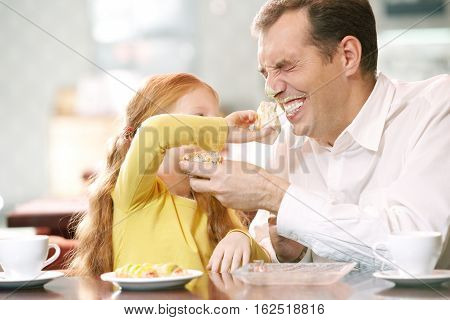 Father and his little daughter fooling about at cafe