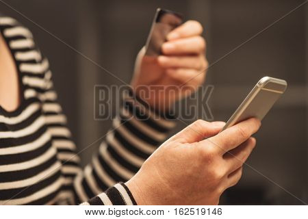 Woman using smart phone to load e-wallet account female hands with mobile phone and credit card making online payment and transfering funds from one e-banking user to another.
