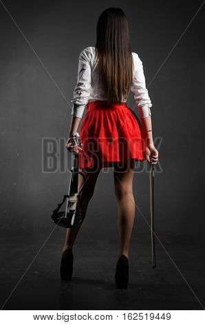 Girl stands back to the photographer with violin. In the red skirt long hair long legs