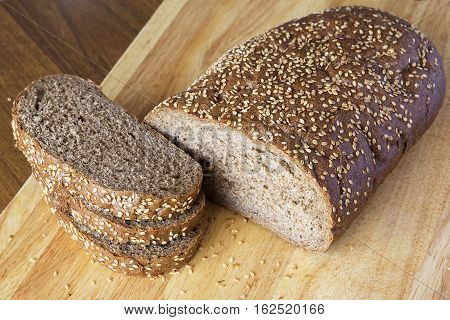 Bread with sesame grains on a wooden table. The cut long loaf
