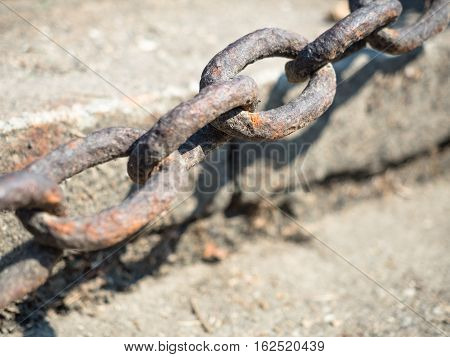 Picture of the selective focus on a rusty iron chain against the blurred background of the gray stones. Rusty iron chain close up.