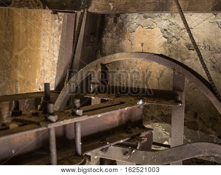 Picture of the rusty mechanism in the wooden belfry of the church. Rusty mechanism for church bell against the old yellow wall of the belfry.