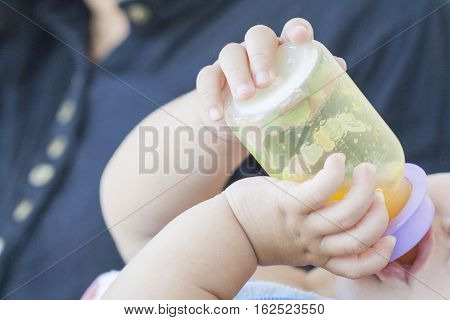 hand of baby holding orange juice bottle suck in embrace mother