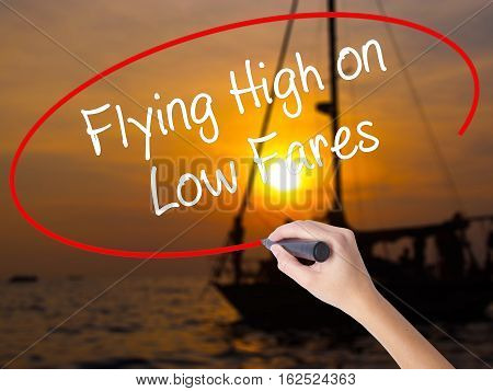 Woman Hand Writing Flying High On Low Fares With A Marker Over Transparent Board