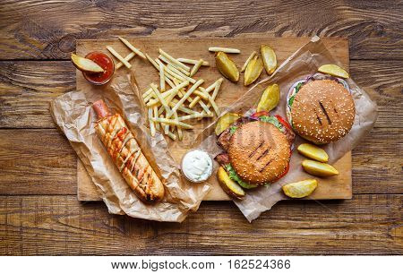 Fast food dish top view. Meat burger, potato chips and wedges with hot dog. Take away composition. French fries, hamburger, mayonnaise and ketchup sauces on wood. Menu or receipt mockup