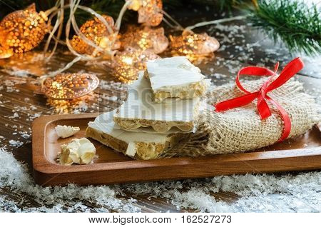 Turron traditional Spanish sweet consumed at Christmas in Spain. Almond nougat dessert served in wooden plate Christmas tree with garland and snow on the background.
