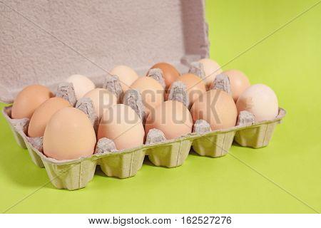Egg Carton Full Of Brown Eggs On Green Background