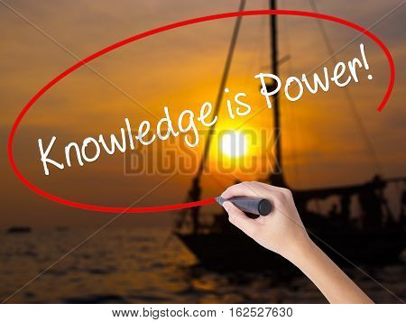 Woman Hand Writing Knowledge Is Power With A Marker Over Transparent Board