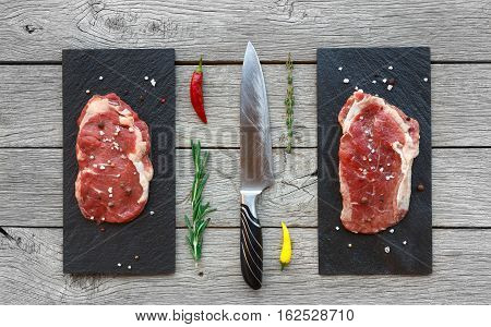 Raw beef steaks on dark wooden table background, top view. Fresh juicy meat with herbs, rosemary and cutting knife on stone boards. Cooking ingredients, butcher's and grocery concept