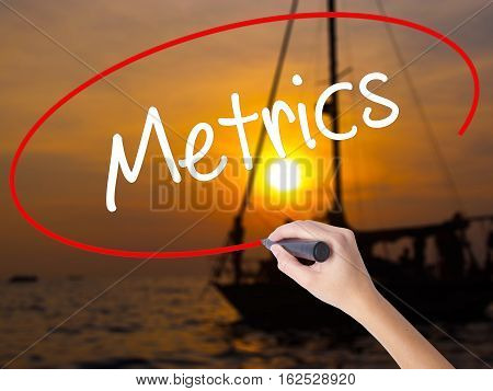 Woman Hand Writing  Metrics  With A Marker Over Transparent Board