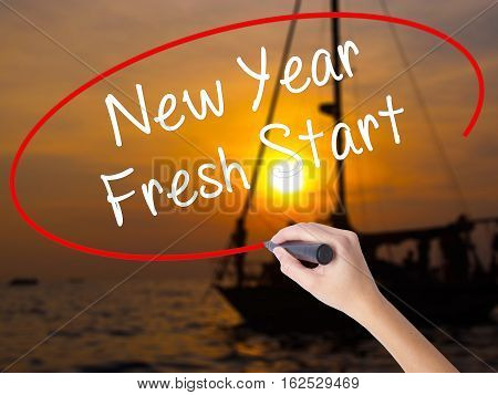 Woman Hand Writing New Year Fresh Start With A Marker Over Transparent Board