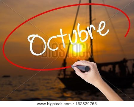 """Woman Hand Writing """"octubre"""" (in Spanish: October) With A Marker Over Transparent Board"""