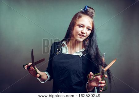 Crazy playful young beautiful fashionable woman with curly hair holding scissors cutting curle