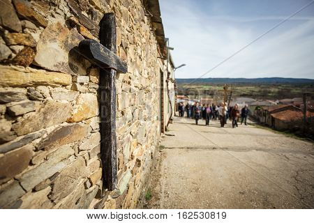 Wide angle view of wooden cross and out of focus people in procession