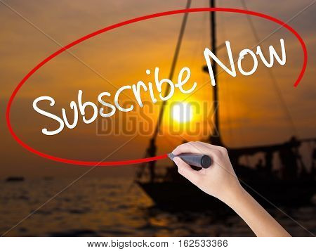 Woman Hand Writing Subscribe Now With A Marker Over Transparent Board