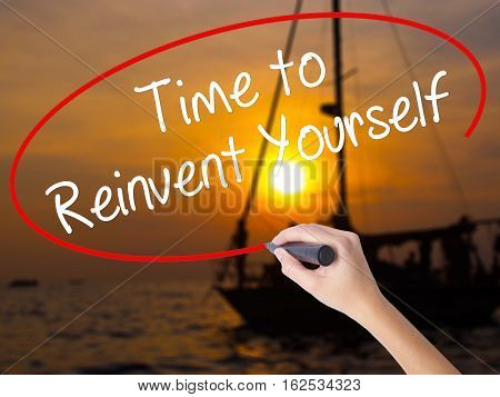 Woman Hand Writing Time To Reinvent Yourself With A Marker Over Transparent Board