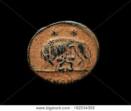 Ancient Roman Commemorative Coin With Image Of Romulus, Remus And Wolf Isolated On Black
