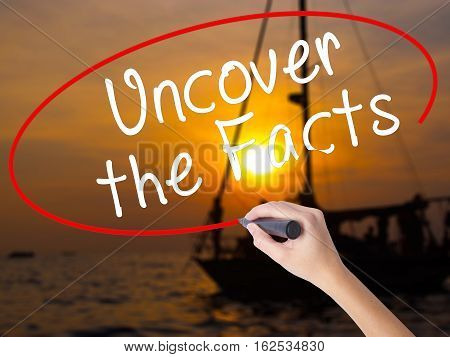 Woman Hand Writing Uncover The Facts With A Marker Over Transparent Board