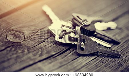Bunch of keys lies on a wooden table.
