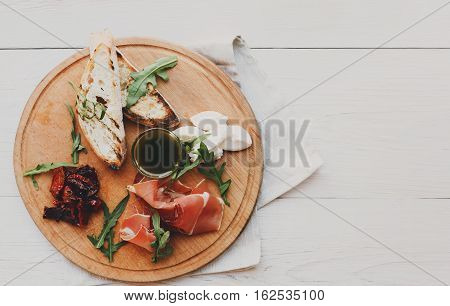 Catering platter antipasto with ham prosciutto, bruschetta bread toasts and mozzarella cheese on round wooden board on white wood table top view with copy space. Served starter meals, restaurant food